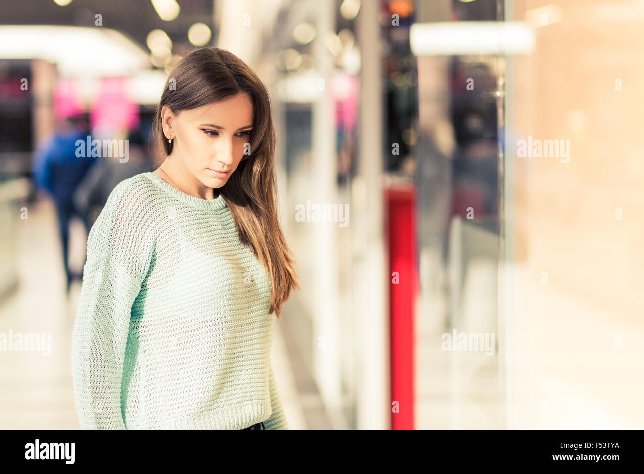 Young caucasian woman with dark brown hair looking through window in the mall. Window shopping background. Warm - Stock Image
