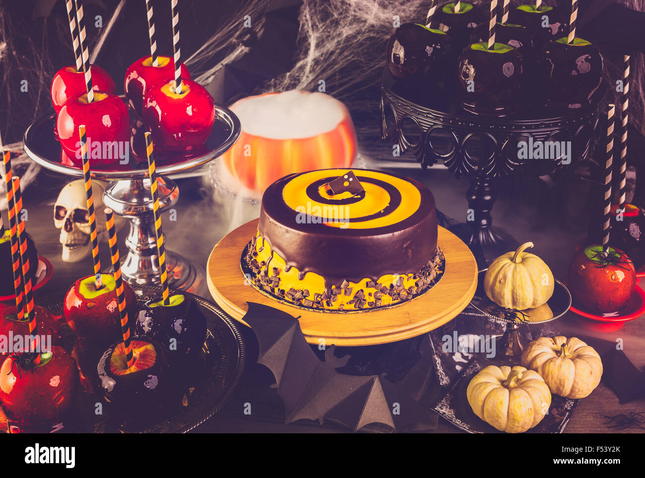 Table With Colored Candy Apples And Cake For Halloween Party Stock