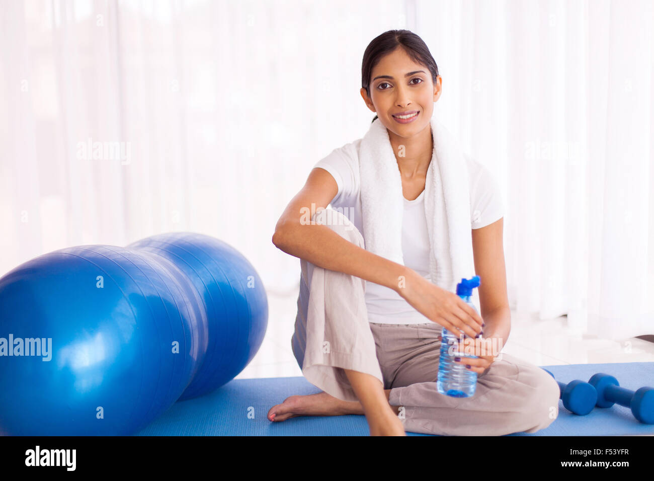 pretty Indian woman sitting on mat after working out at home - Stock Image