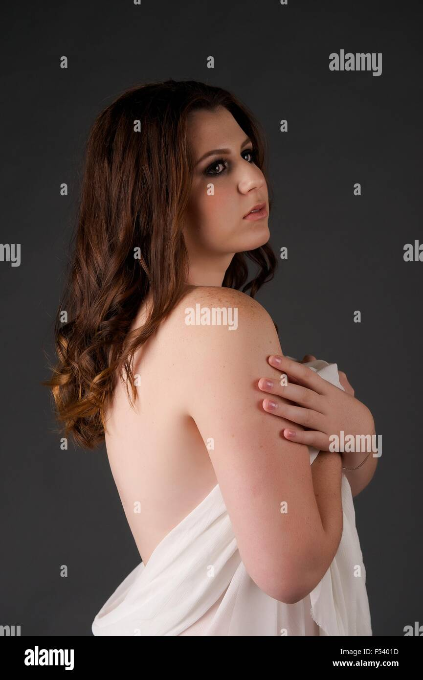 Young Brunette girl stands in the studio wrapped in tulle drape - her back is uncovered and she faces to camera - Stock Image
