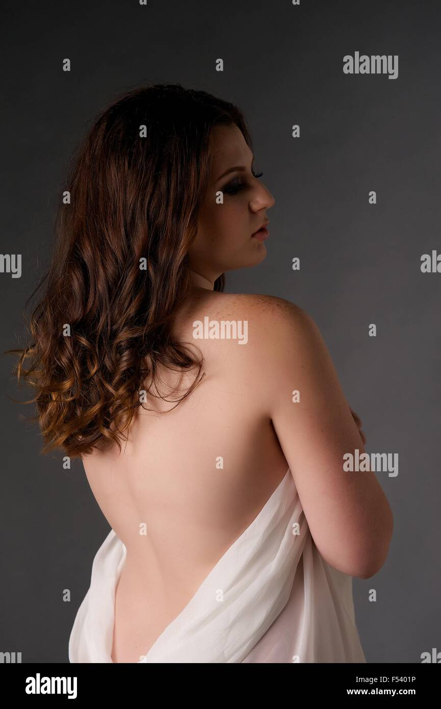 Young Brunette girl stands in the studio wrapped in tulle drape - her back is uncovered and she faces away - Stock Image