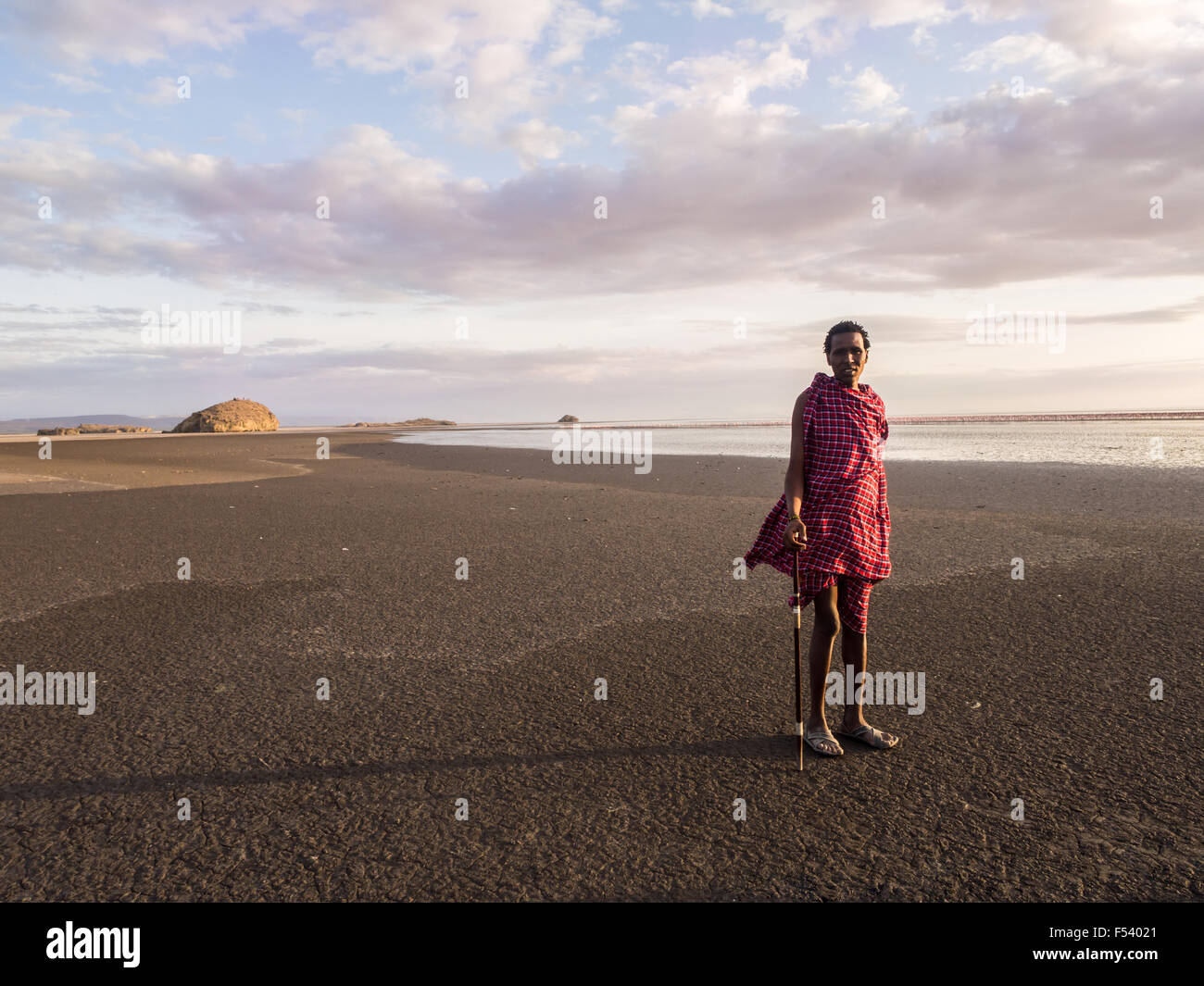 Maasai guide leading tourists to visit Lake Natron in the north of Tanzania, Africa, at sunrise. - Stock Image