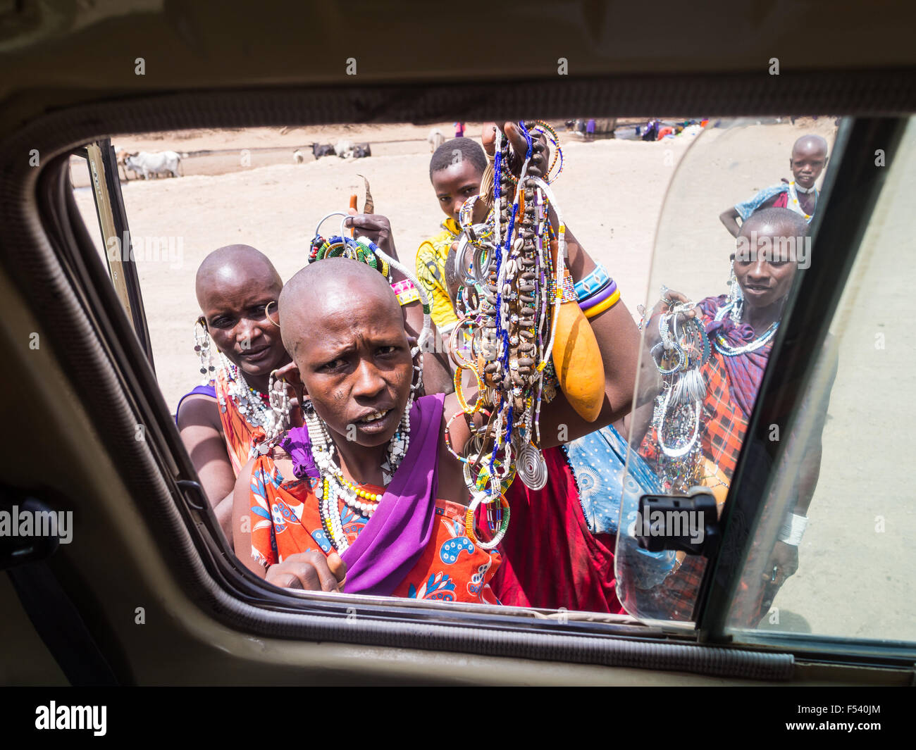 Maasai women offering souvenirs to the tourists through a car window in  Arusha region 4e9b4af3d1