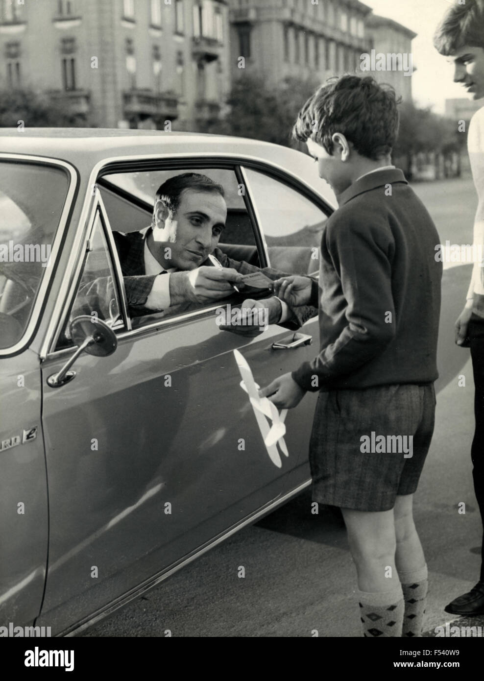 The Italian presenter Pippo Baudo signs an autograph for a child - Stock Image