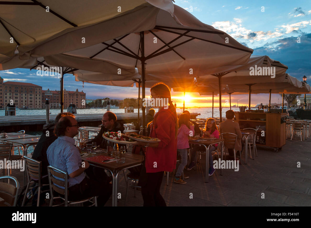 Dining by Canale Della Giudecca at OKE pizza restaurant at sunset in Venice, Italy - Stock Image