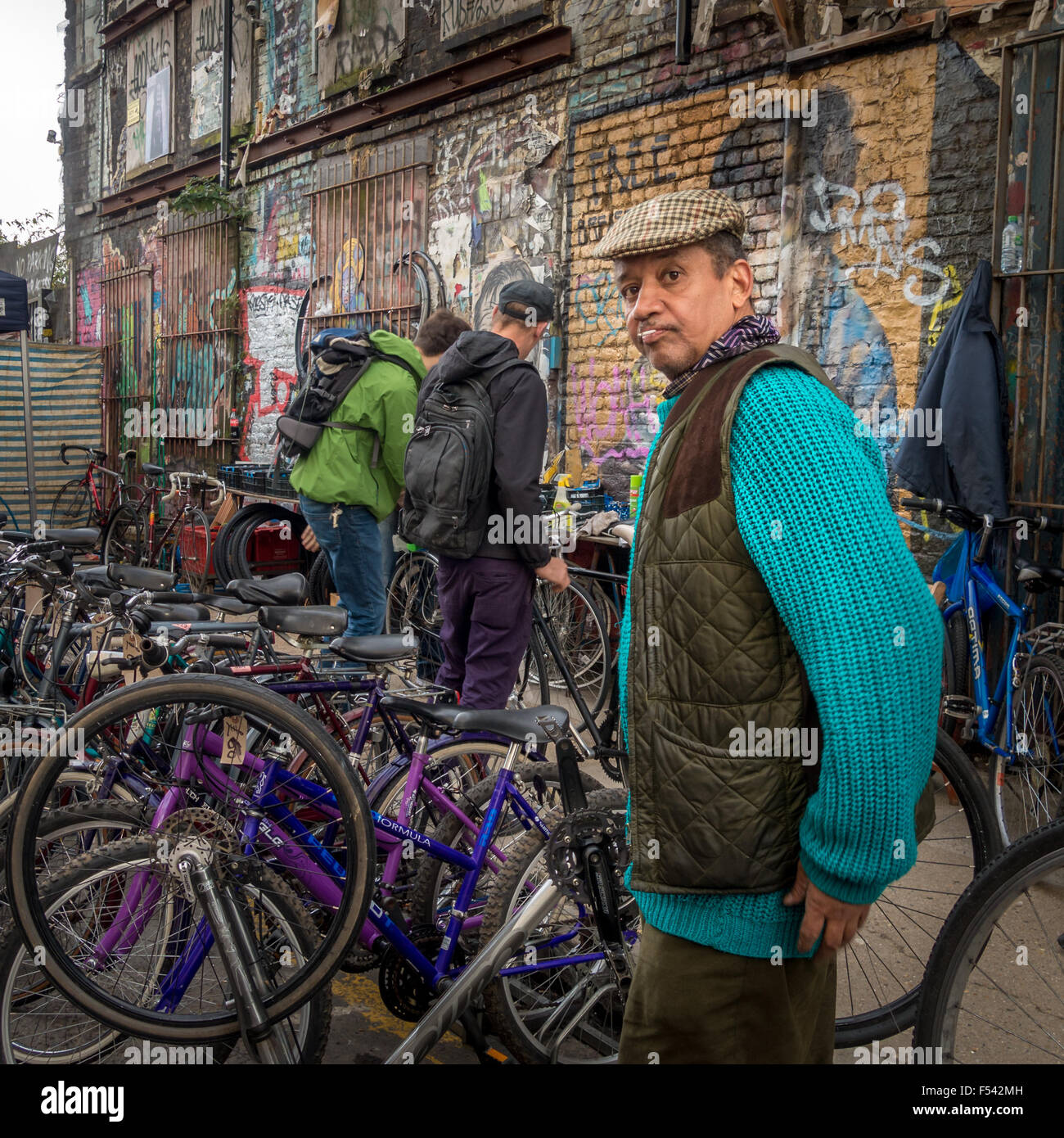 Street seller selling second hand bikes on Sclater Street, off Brick Lane in the East End of London. - Stock Image