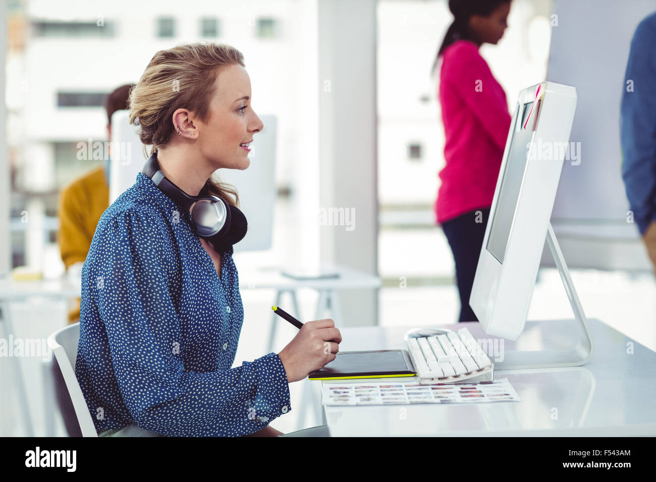 Graphic designer wearing headphones at desk - Stock Image
