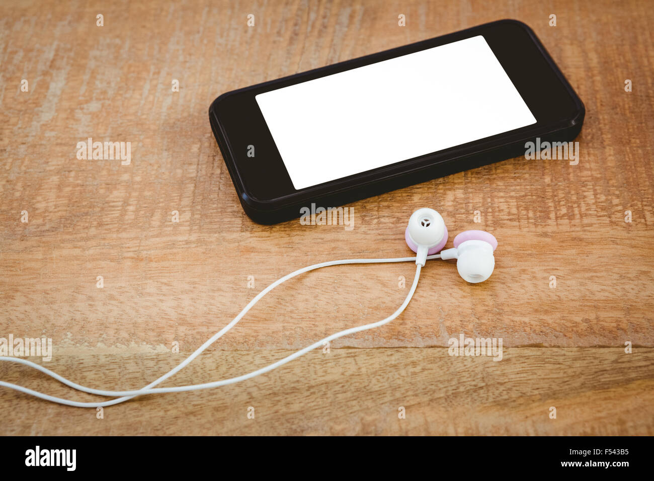 Black smartphone with white headphones - Stock Image