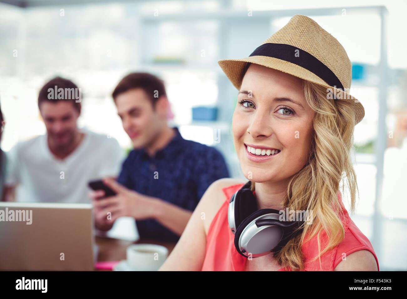 Smiling creative businesswoman working with co-workers - Stock Image