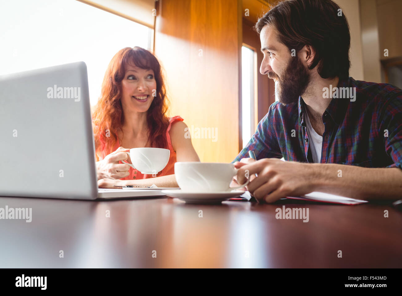 Students chatting in the cafe using laptop - Stock Image