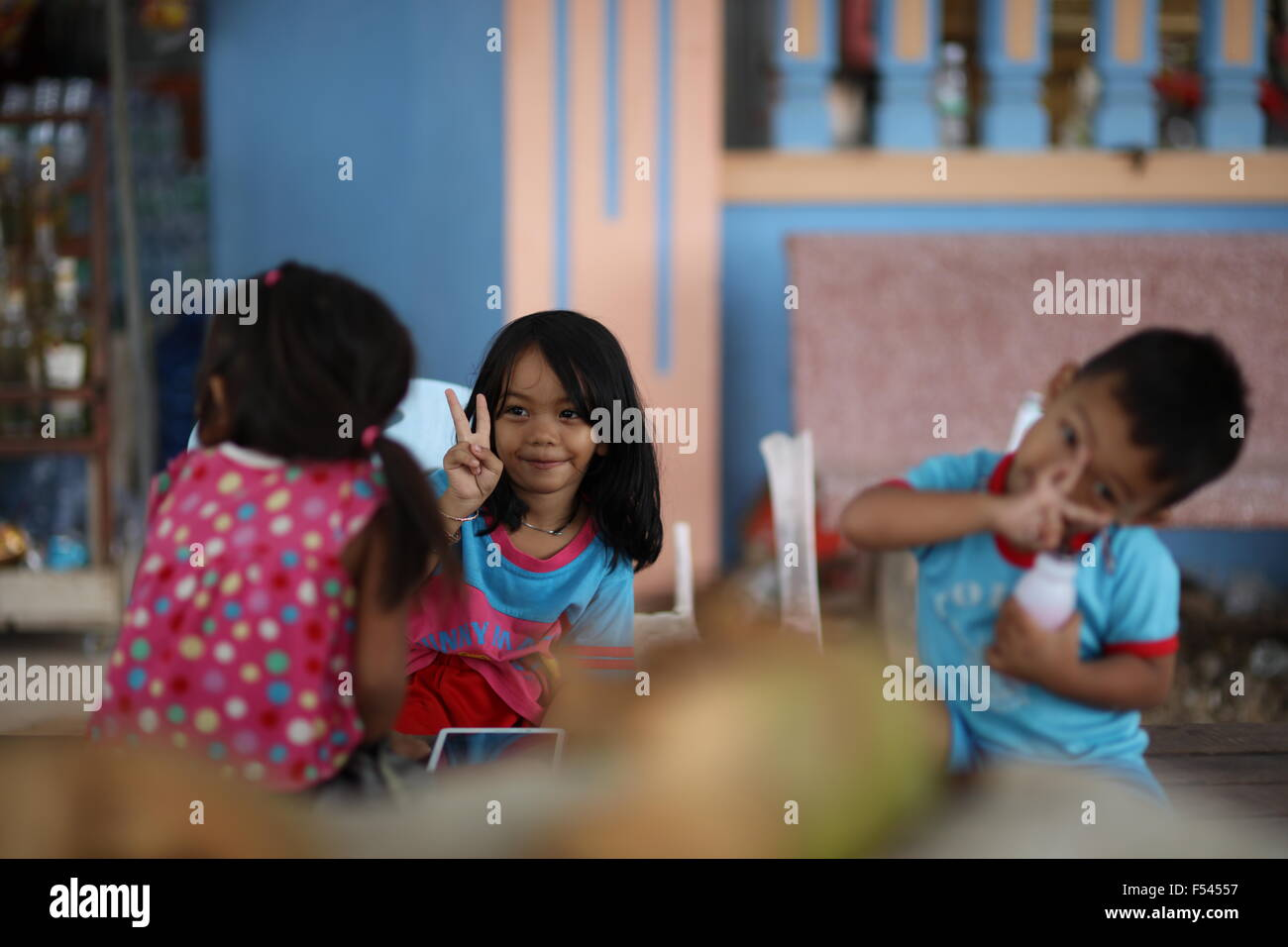 Girl in focus showing victory sign to other girl, a little boy trying to mimik her Stock Photo