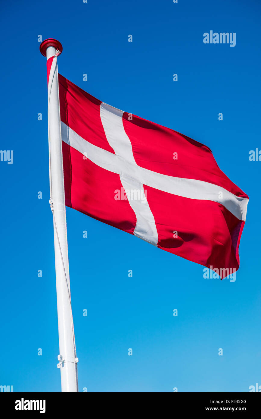 Danish flag on a flag pole in the wind - Stock Image
