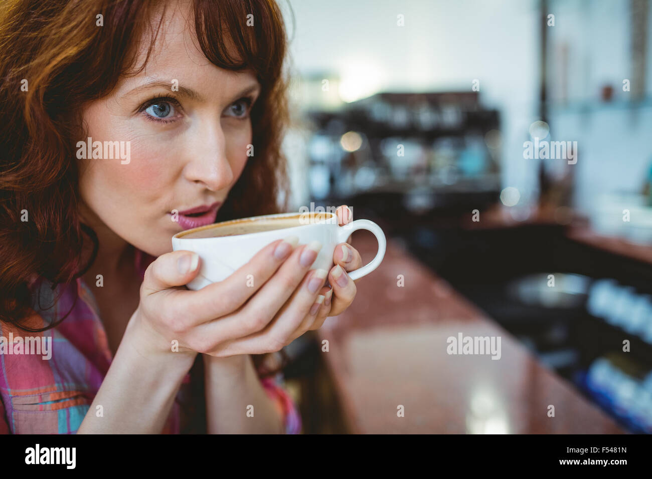Mature student sipping her coffee - Stock Image