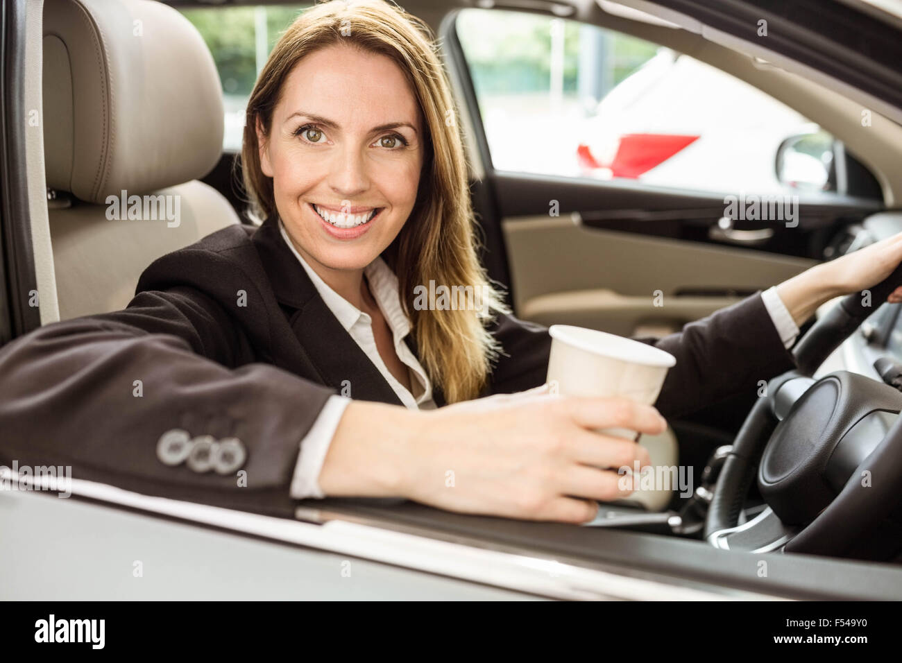 Smiling businesswoman siting in a car - Stock Image