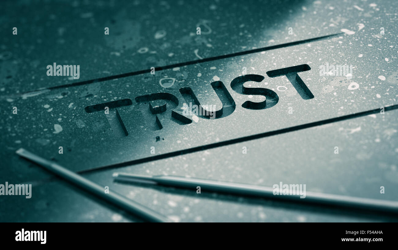 Word trust engraved in black stone with tools and blur effect. Concept image for illustration of strong relationship - Stock Image
