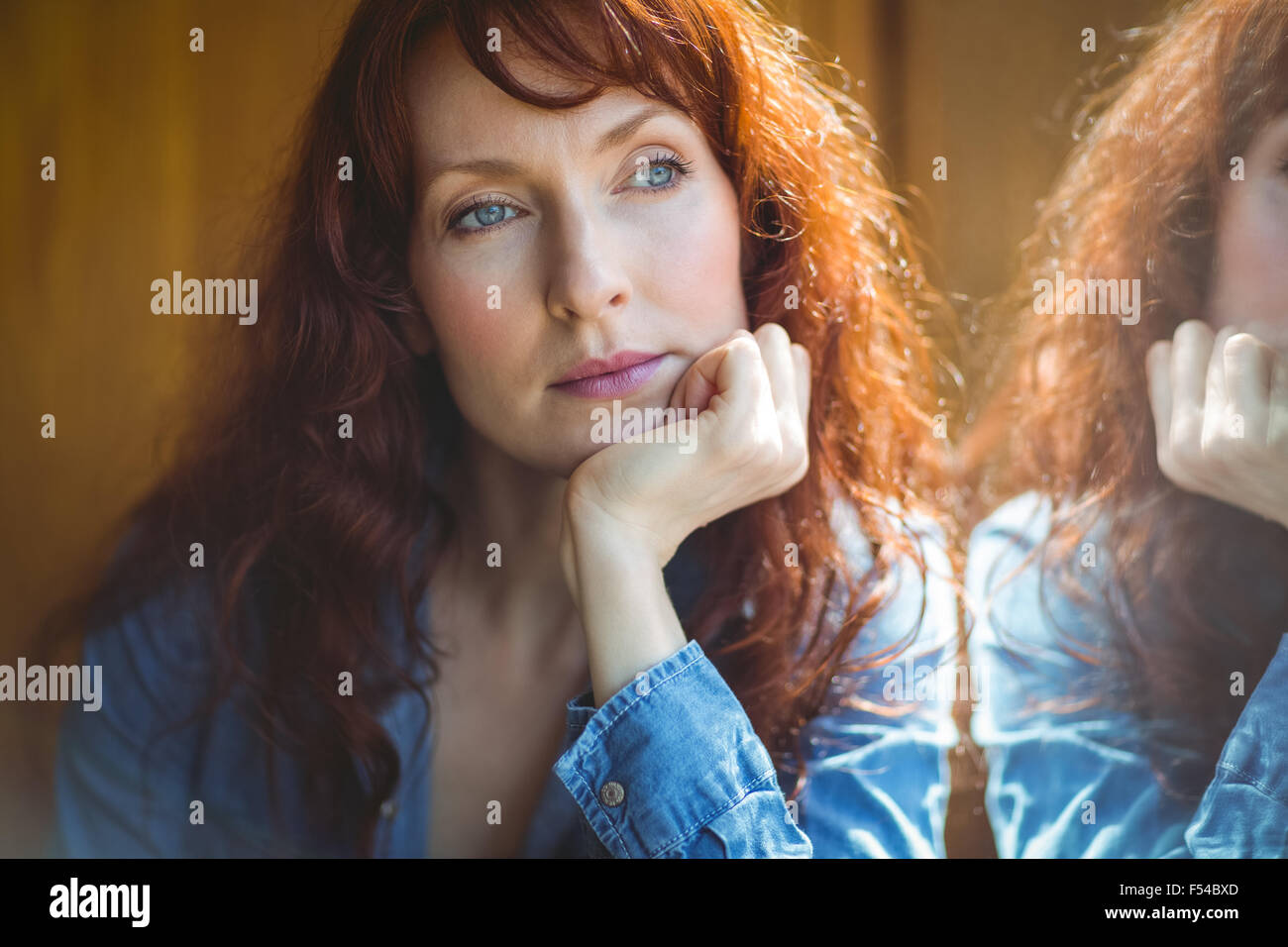 Mature student thinking in cafe - Stock Image