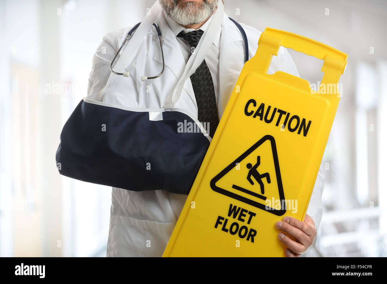 Senior doctor holding caution sign while wearing elbow sling inside building - Stock Image