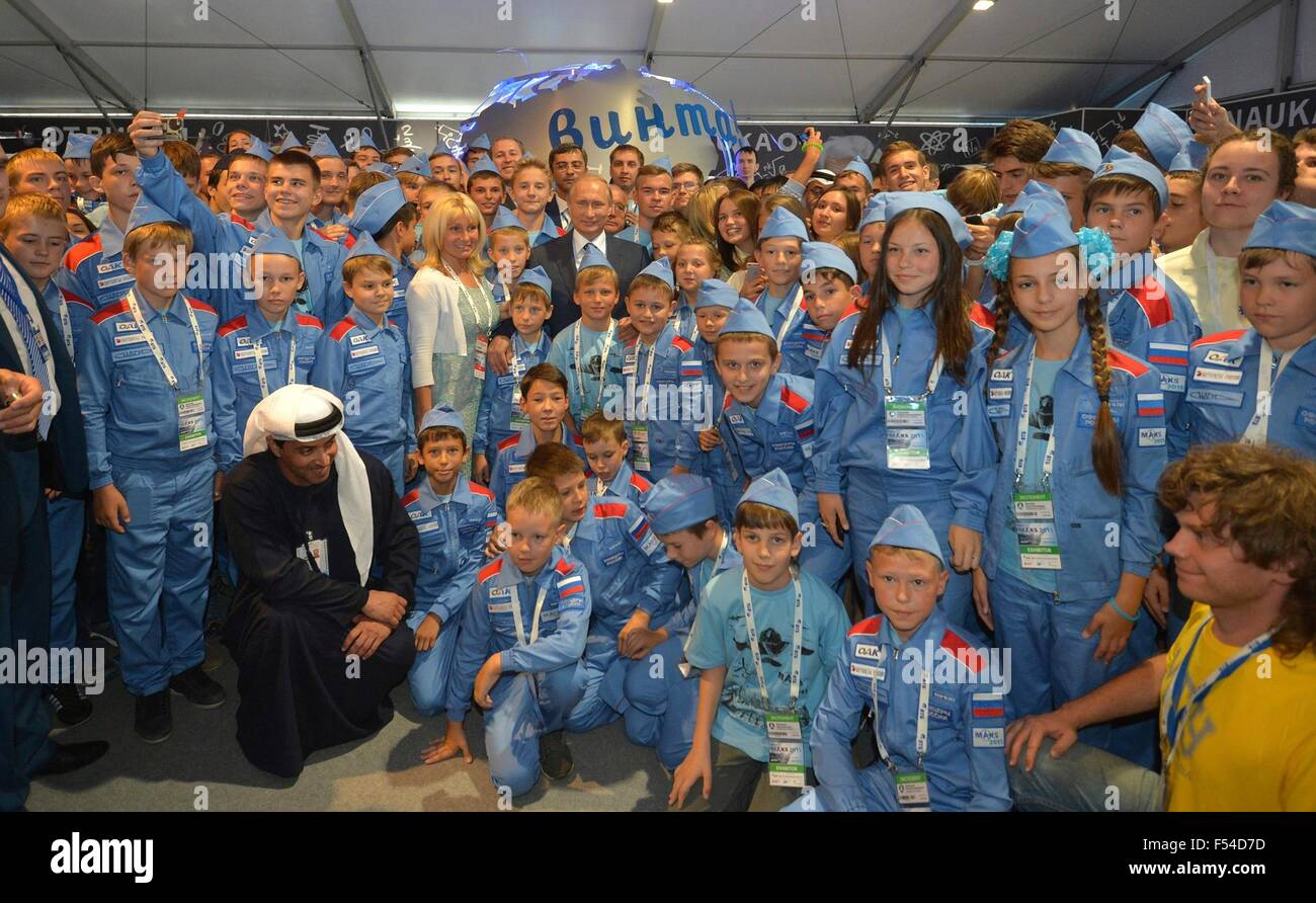 Russian President Vladimir Putin poses with students at the exhibition Ot vinta or Clear Prop during the International - Stock Image