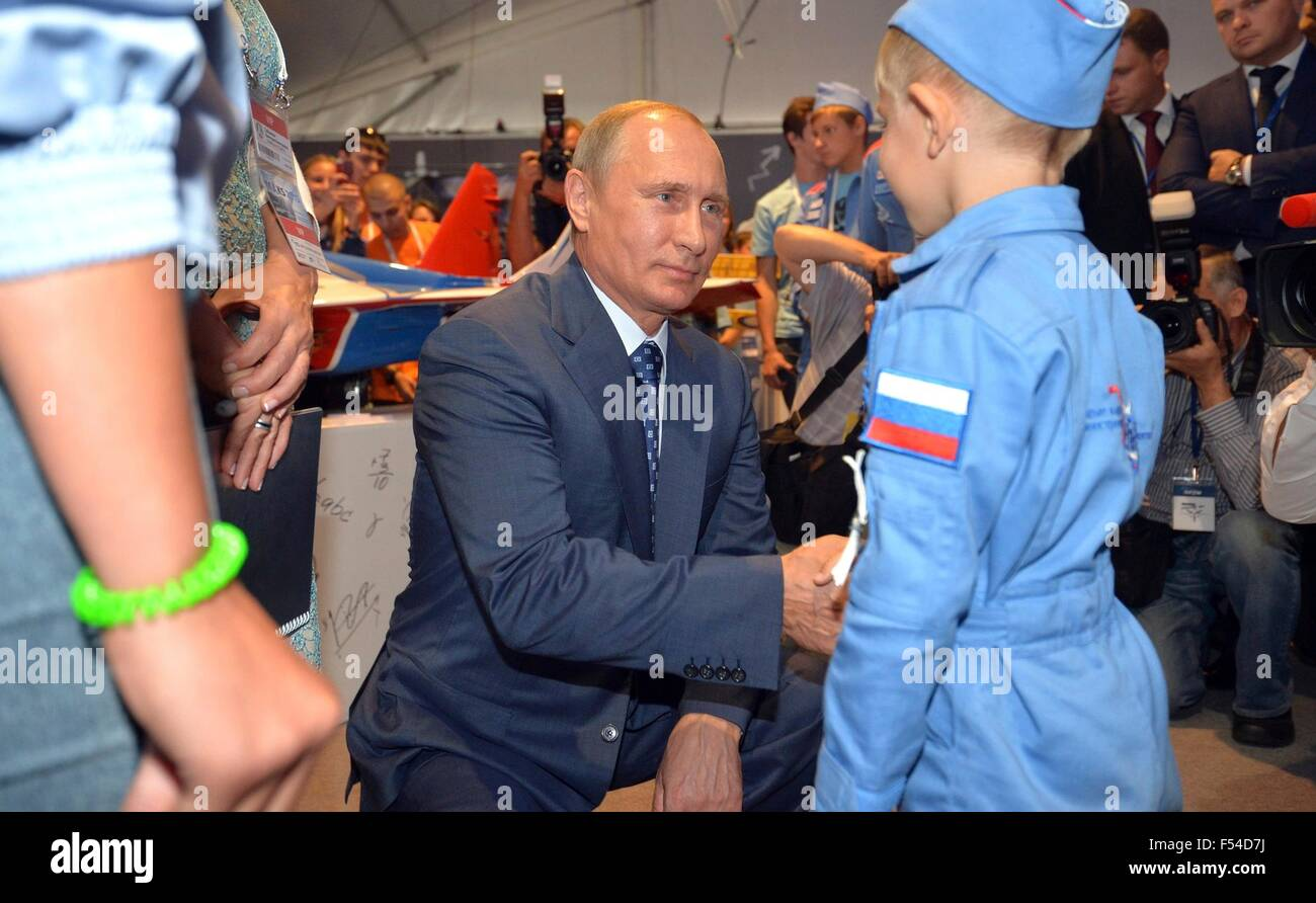 Russian President Vladimir Putin greets a young boy at the exhibition Ot vinta or Clear Prop during the International - Stock Image