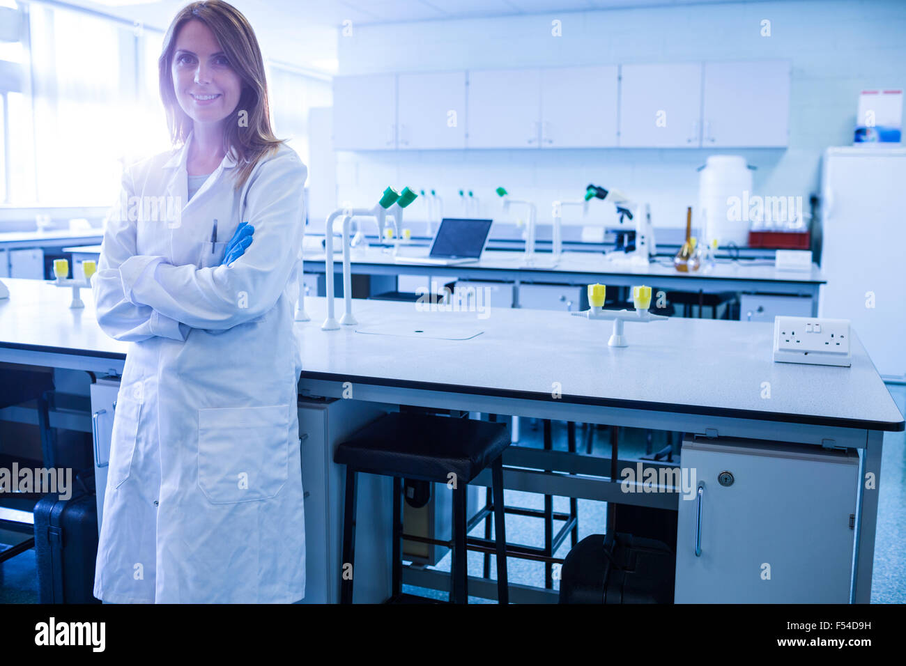 Scientist smiling at the camera in lab - Stock Image