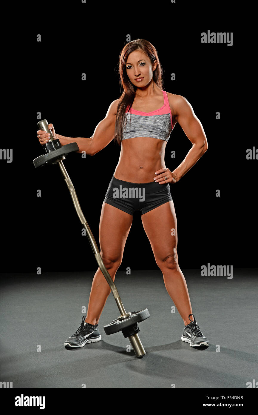 Beautiful young woman holding barbell over dark background - Stock Image