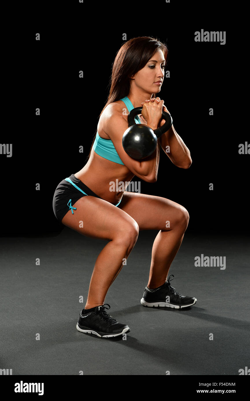 Young woman exercising with kettlebell over dark background - Stock Image