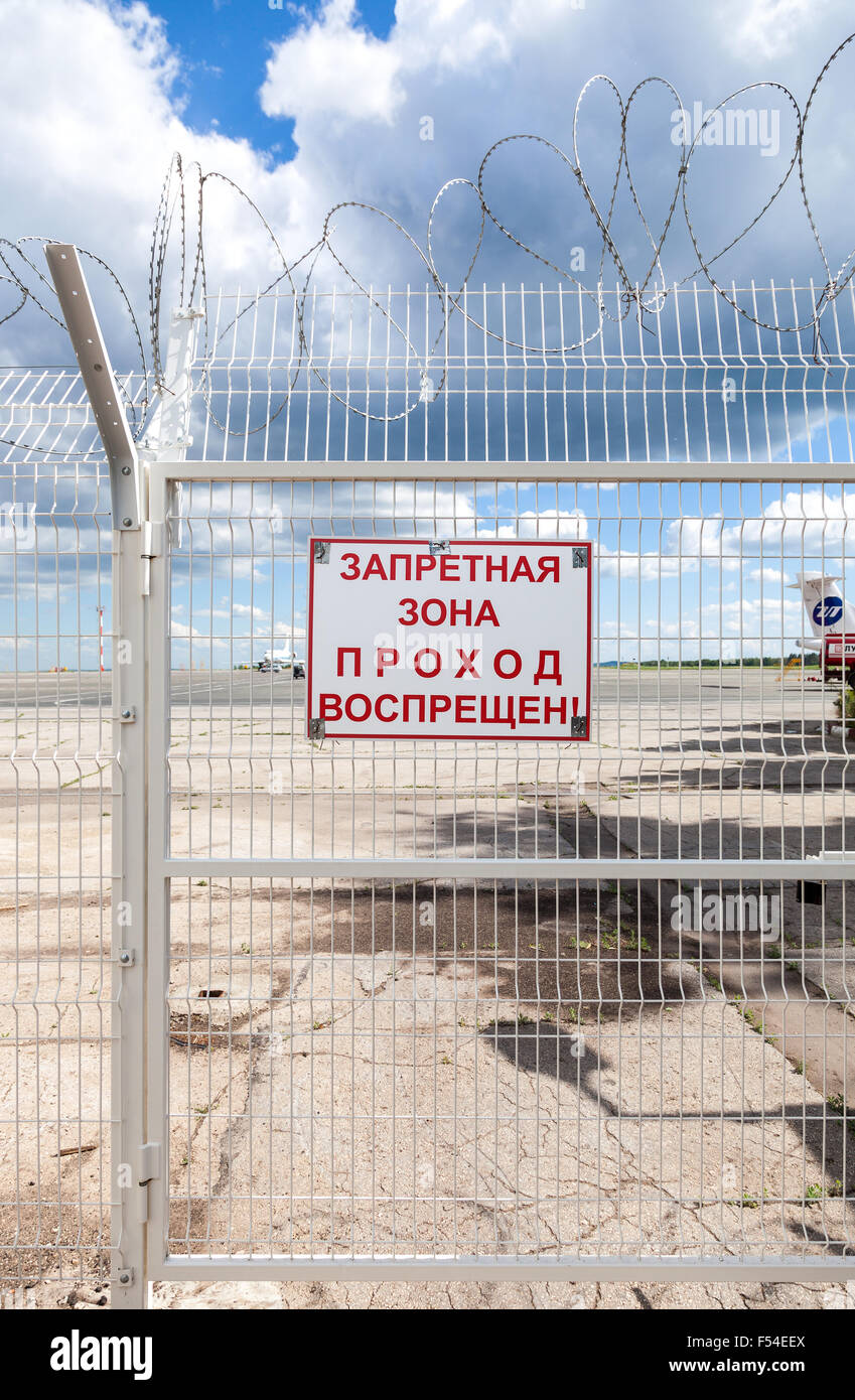Security fence in russian airport. Text on russian: 'Forbidden Zone, the passage is prohibited' - Stock Image