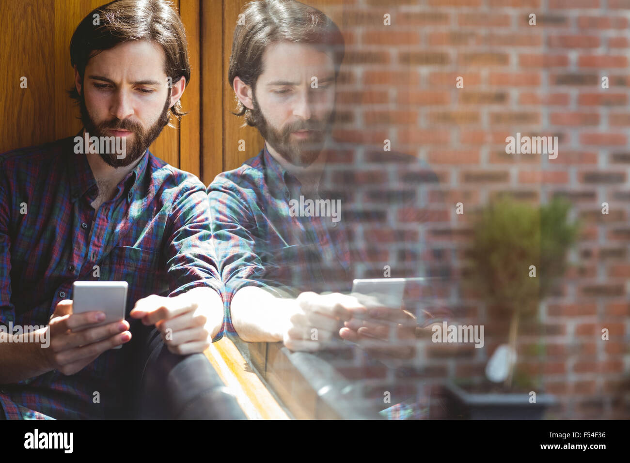 Hipster student sending text in canteen Stock Photo