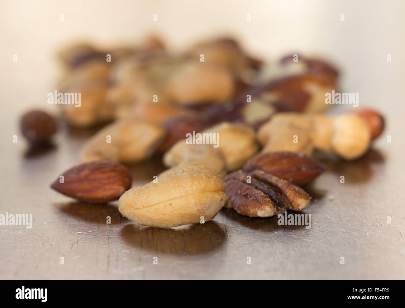 Mixed nuts on a rustic wooden table - Stock Image