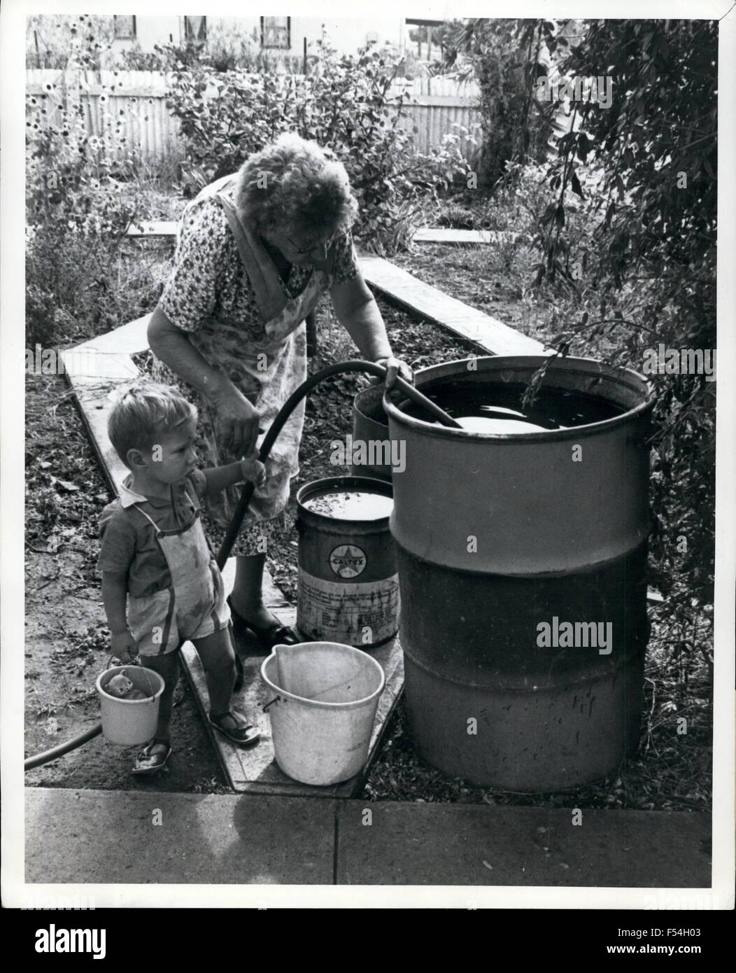 1968 - Mrs. E.J.Dwyer, watched by grandson Raymond Colvin, fills her 44-galon drum after the arrival of the Tullibigeal - Stock Image