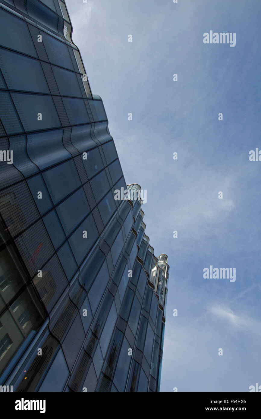 A building in Central London designed with curved glass looking upwards on a day with blue sky - Stock Image