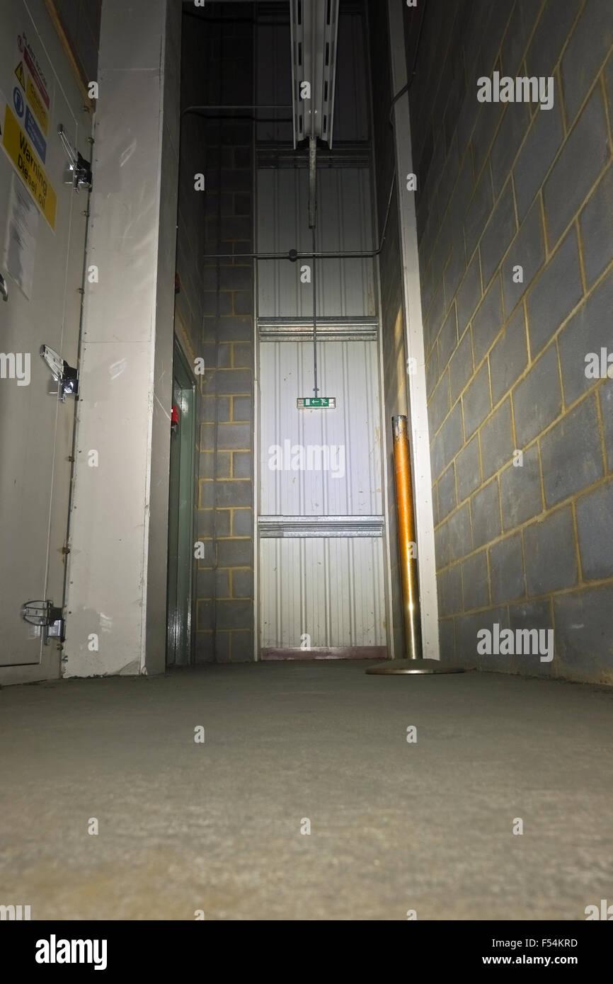 Poorly lit corridor and exit door UK - Stock Image
