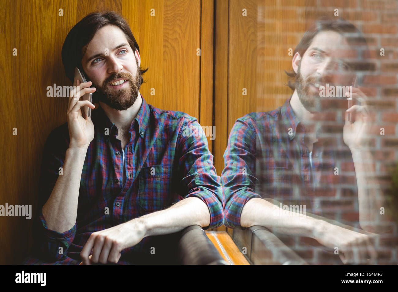 Hipster student on a call in canteen - Stock Image