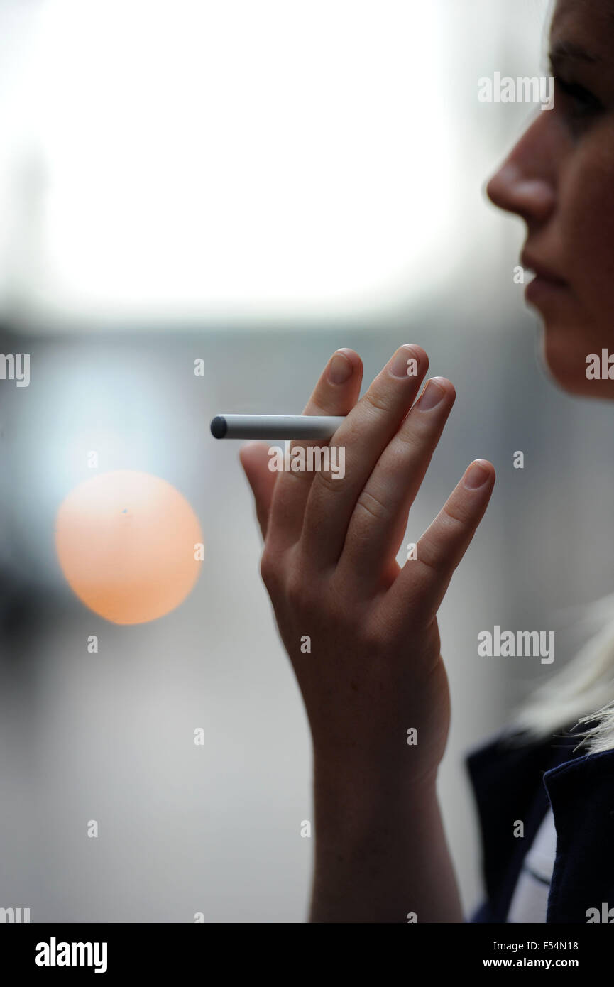 A girl smoking an e-cigarette ecig vaping. - Stock Image