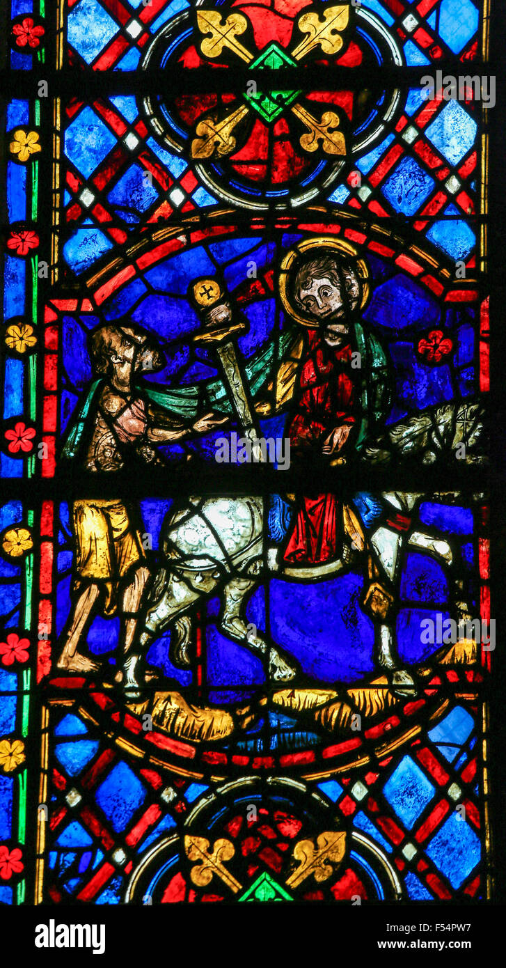 Stained glass window depicting Saint Martin of Tours cuting a piece of his cloak for a beggar in the Cathedral of Stock Photo