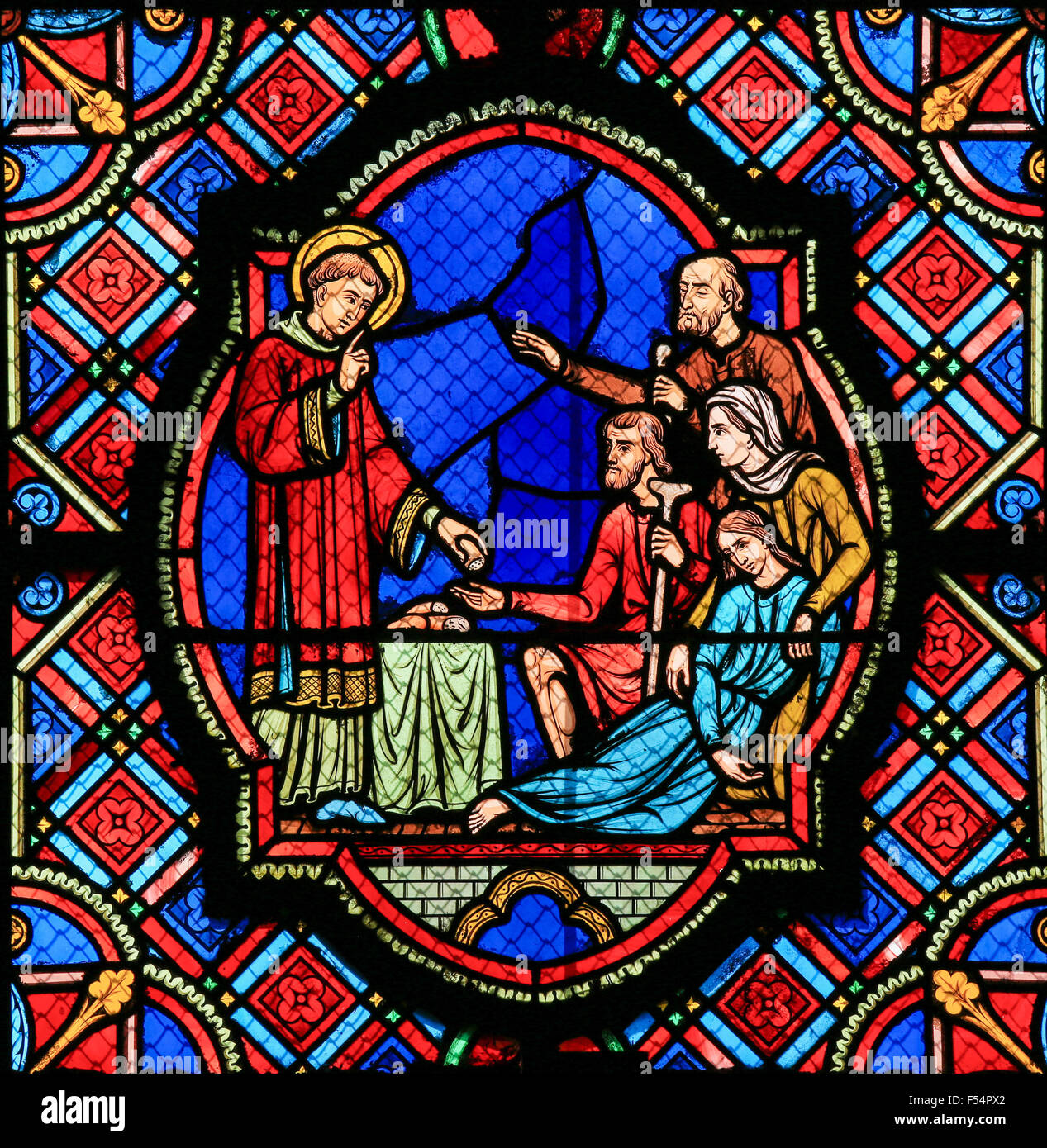 Stained glass window depicting a Saint handing out bread in the Cathedral of Tours, France. - Stock Image