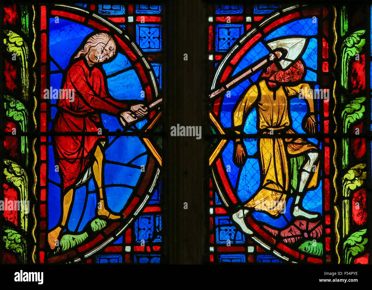 Stained glass window depicting one person hitting another with a spade in the Cathedral of Tours, France. - Stock Image