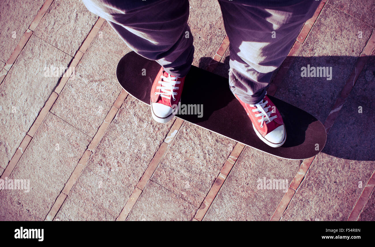 self-portrait of a young man wearing red sneakers on a skate board - Stock Image
