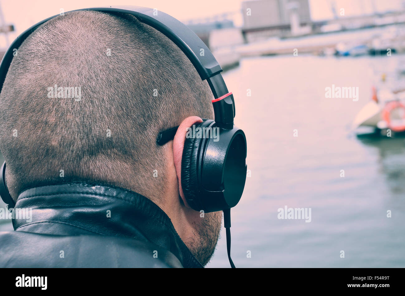 closeup of a young caucasian man seen from behind listening to music with headphones in front of the sea, with a - Stock Image
