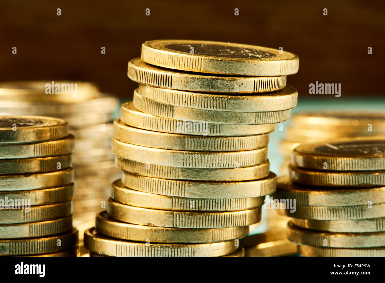 closeup of some piles of coins of one euro - Stock Image