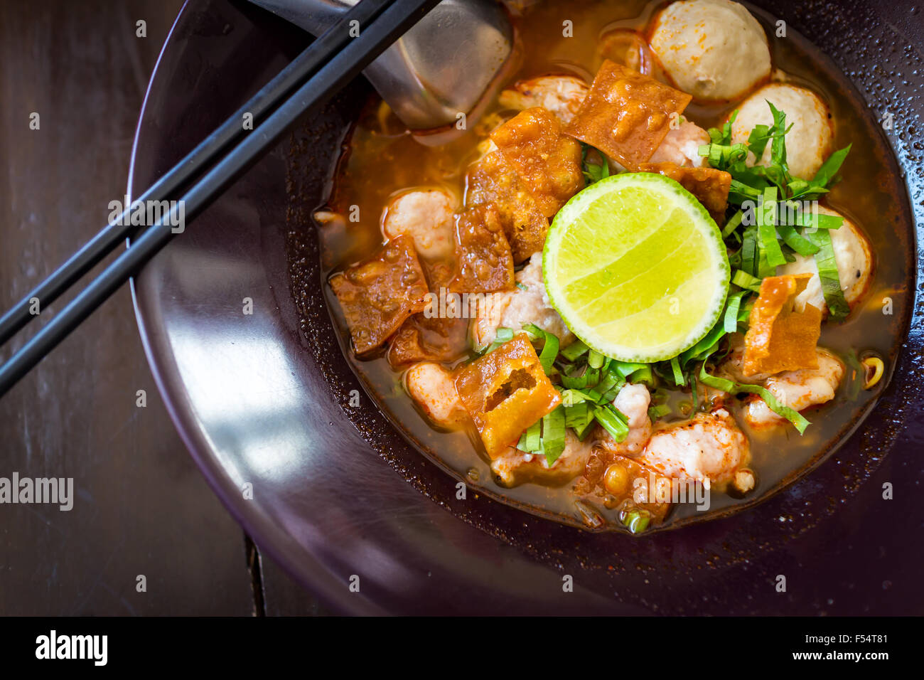 Thai Noodles spicy tom yum soup with pork and lemon on topping street food in thailand - Stock Image