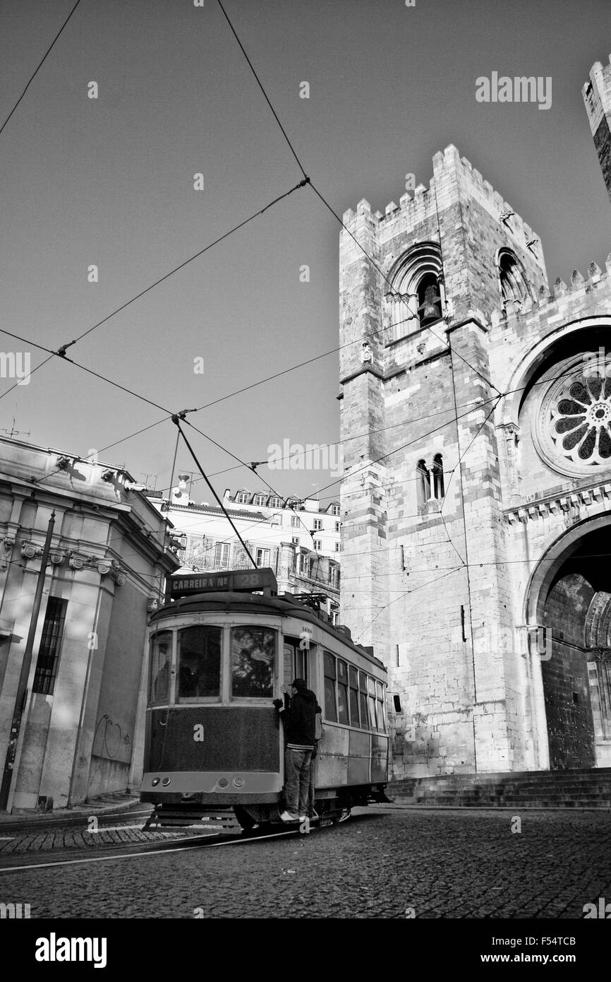 Vintage old tram 28 in Alfama district and Se Cathedral at  bottom with stowaways - Stock Image