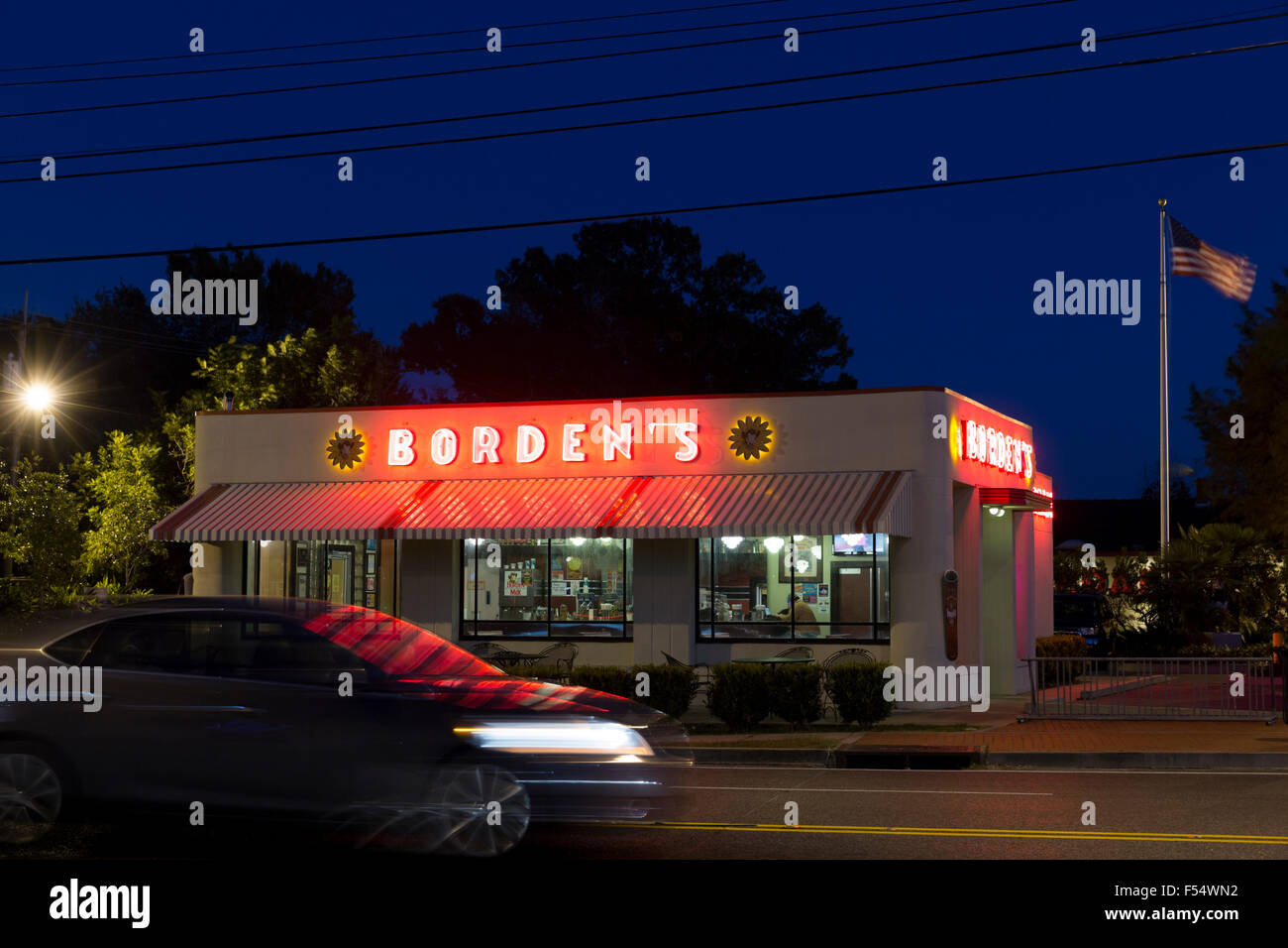 Borden's typical ice cream parlor with Stars and Stripes flag at night in Layfayette,  Louisiana, USA Stock Photo