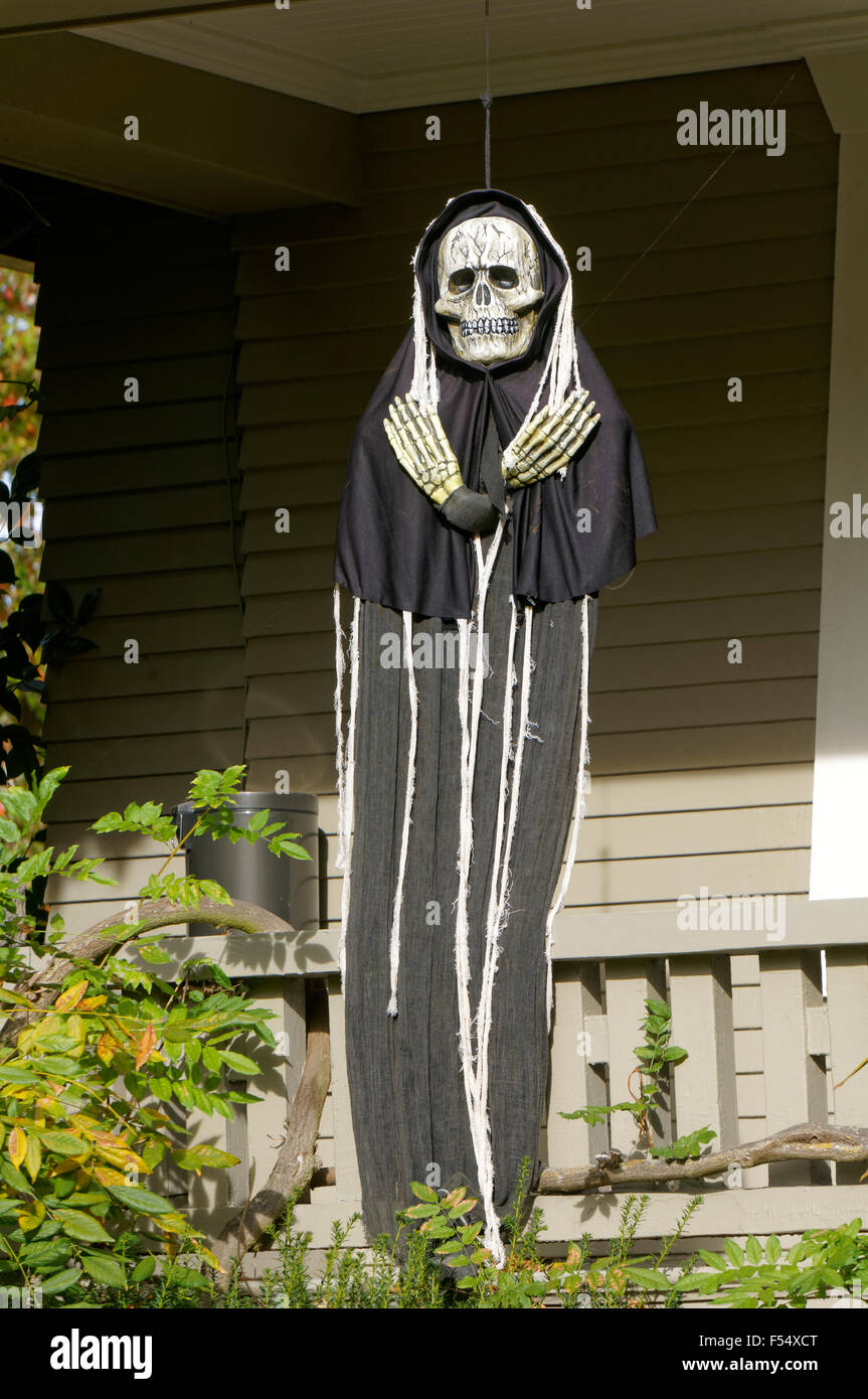 Halloween skeleton dressed in black robe outside a house, Vancouver, BC, Canada - Stock Image