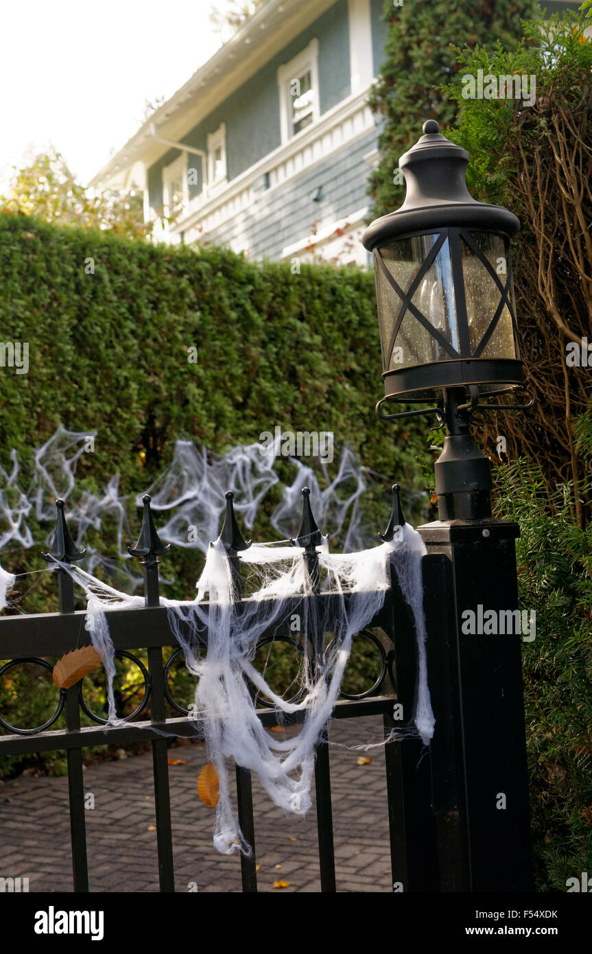 White Halloween spider webs draped on an iron fence in front of an old house, Vancouver, BC, Canada - Stock Image