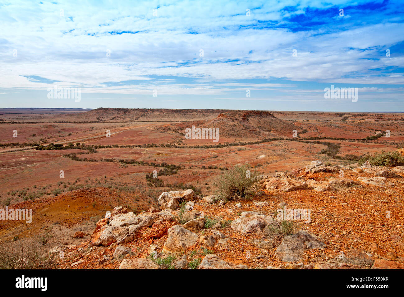 Stunning Australian outback landscape from hilltop lookout, rocky mesas on vast barren treeless red plains stretching - Stock Image