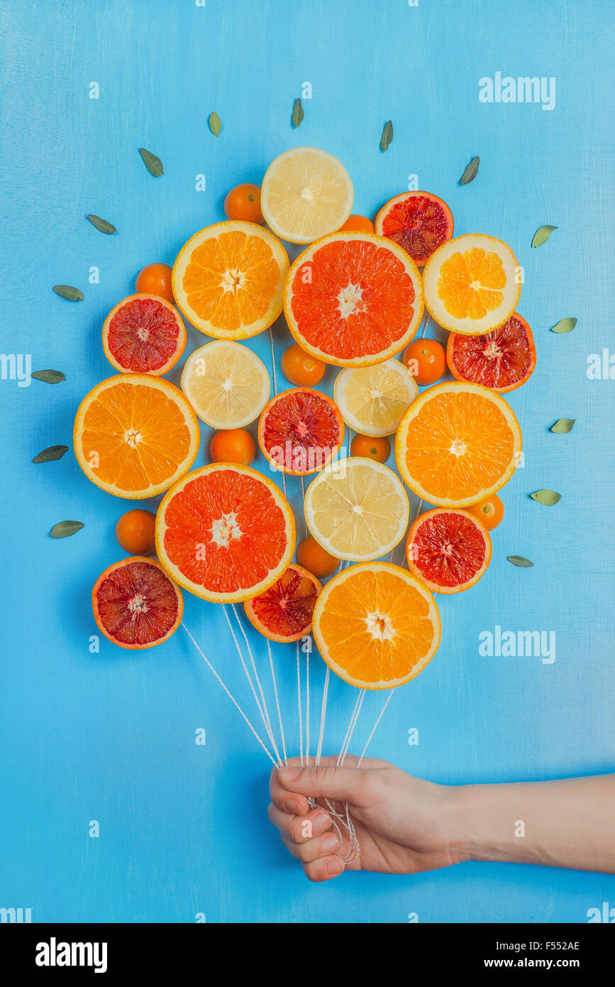 Congratulations on summer! Bouquet of oranges and grapefruits, looking like a bunch of balloons. Sky-blue background. - Stock Image