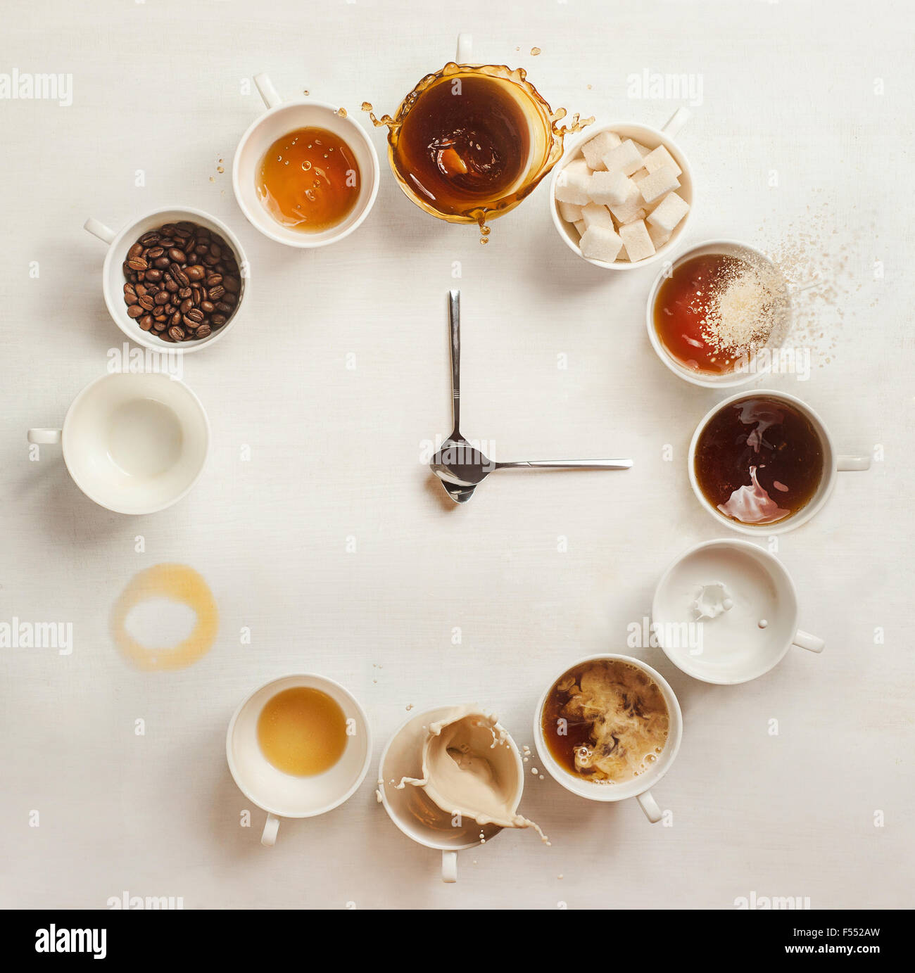 Coffee Clock.Clock made of a dozen cups of coffee (with coffee beans, milk and splashes). It's always coffee - Stock Image