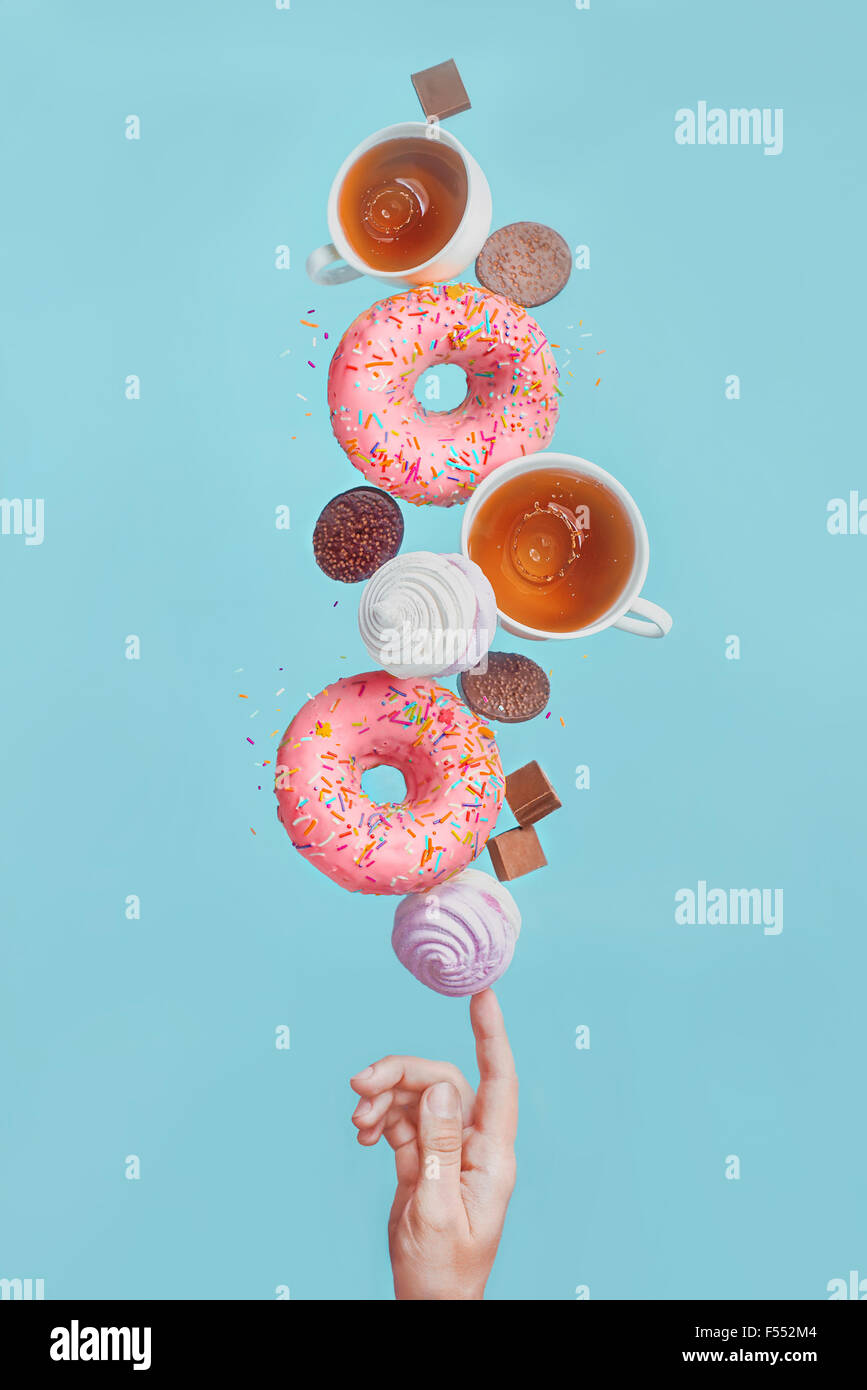Balancing donuts. Glazed donuts, tea cups, marshmallows and chocolate chips, balancing on the tip of one's finger - Stock Image
