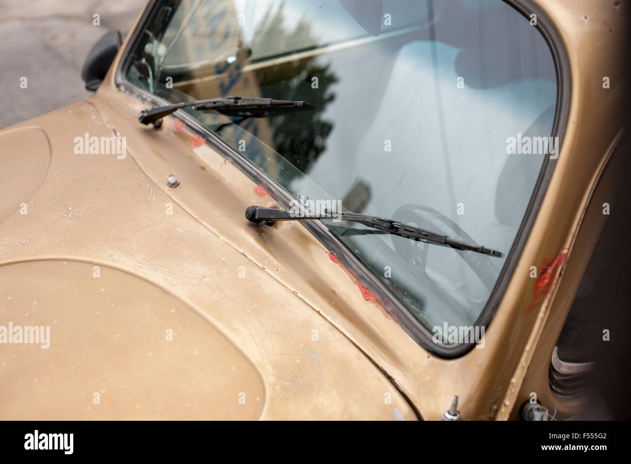 Golden VW beetle car. A rusty old Volkswagen beetle or bug has a coat of dull golden paint.  It is showing cracks. - Stock Image
